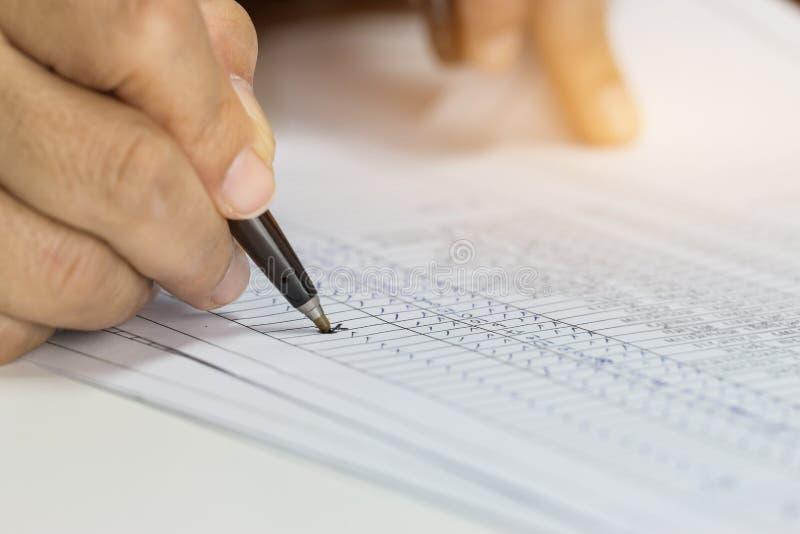 Stylo de participation d'homme d'affaires de main pour écrire les papiers de vérification de rapports au-dessus du formulaire de  photo libre de droits