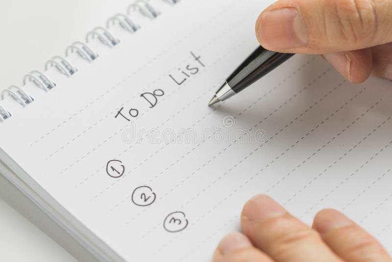 Stylo de participation de main écrivant quoi faire dans personnel pour faire le bloc-notes de liste sur la table blanche employan photos libres de droits