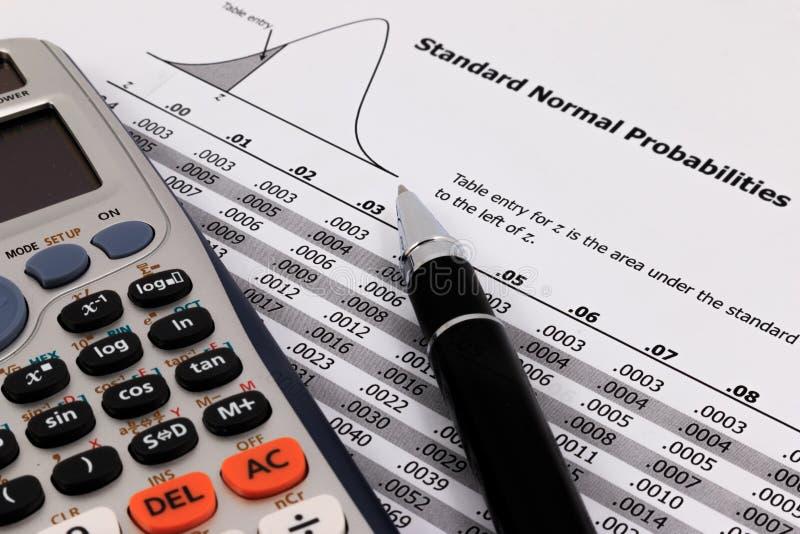 Stylo et calculatrice sur la table normale standard de probabilités photographie stock libre de droits