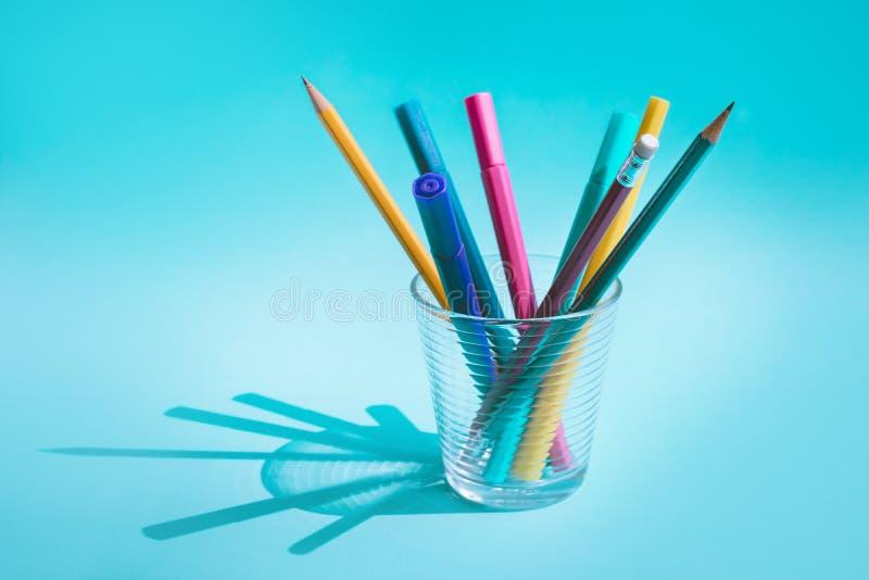 Stylo et crayon colorés en verre avec la longue ombre sur le fond en pastel photo libre de droits