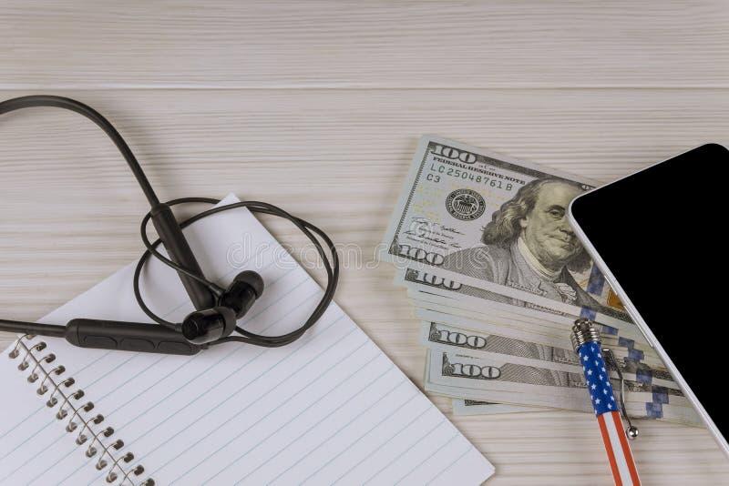 Stylo et papier de smartphone d'écouteurs de dollars US pour votre texte images stock
