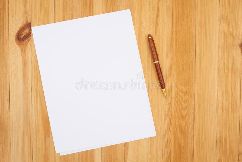 Stylo et papier sur le bureau en bois de pin à texture de grain photographie stock libre de droits
