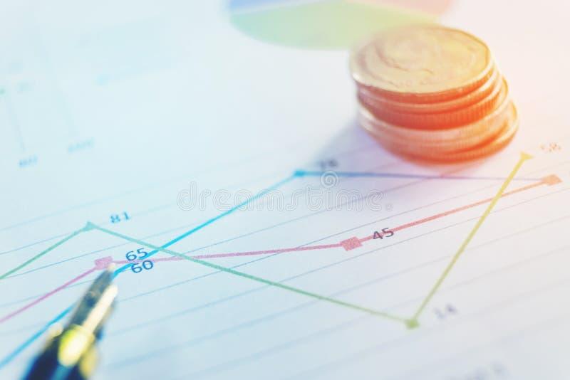 Stylo et pièce de monnaie sur le papier d'affaires Rapportez le diagramme photo libre de droits