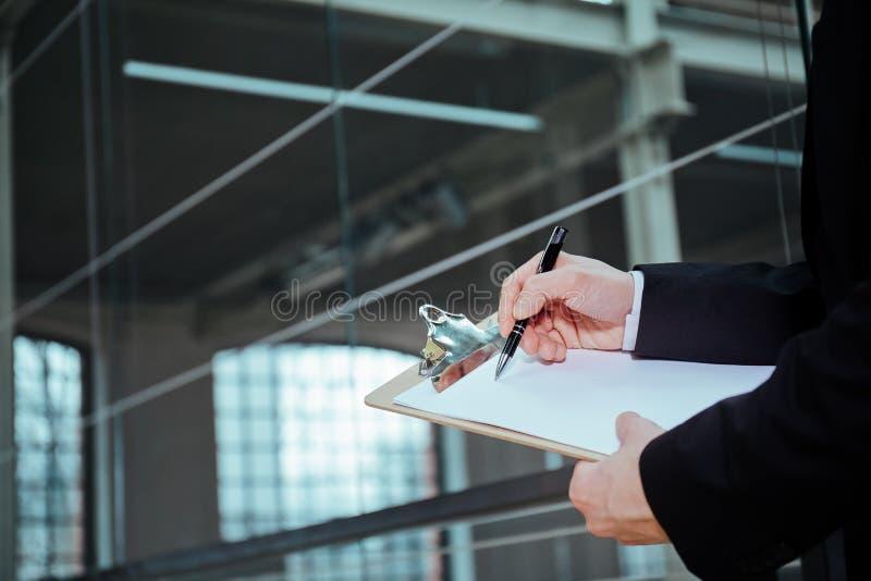 Stylo et presse-papiers de participation d'homme d'affaires images stock