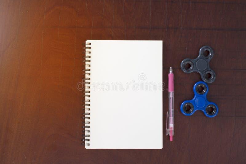 Stylo, fileur de main, carnet sur le fond en bois de table, lig jaune photo libre de droits