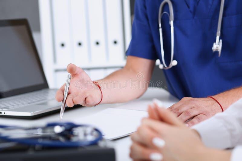 Stylo masculin d'argent de prise de bras de docteur remplissant plaintes patientes photos libres de droits