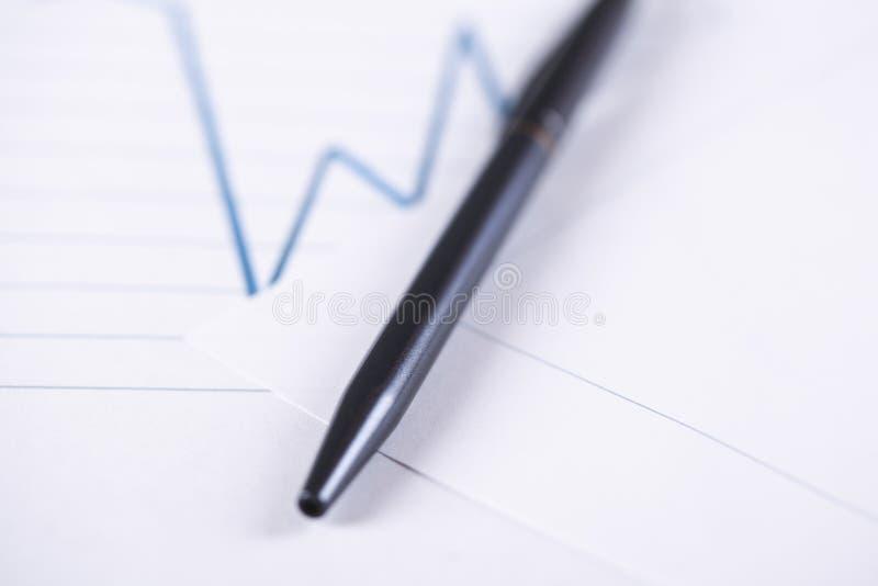 Stylo noir sur le papier de graphique de finances images stock