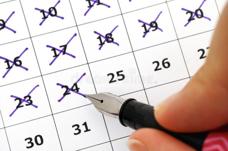 Stylo-plume chez des jours d'inscription de main de la femme dans le calendrier images stock