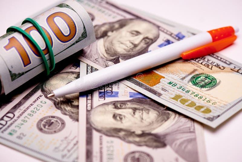 Stylo sur des billets de banque en valeur cent dollars US sur un fond blanc photos libres de droits