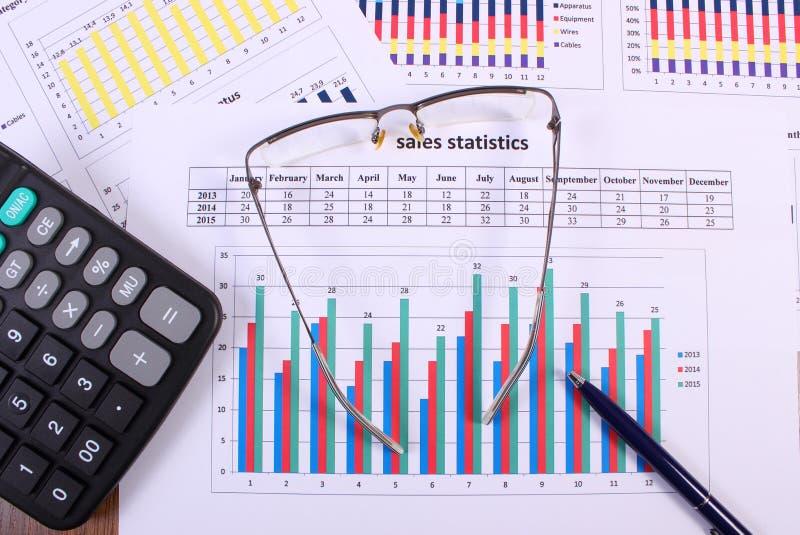 Stylo, verres et calculatrice sur le graphique financier, concept d'affaires images libres de droits