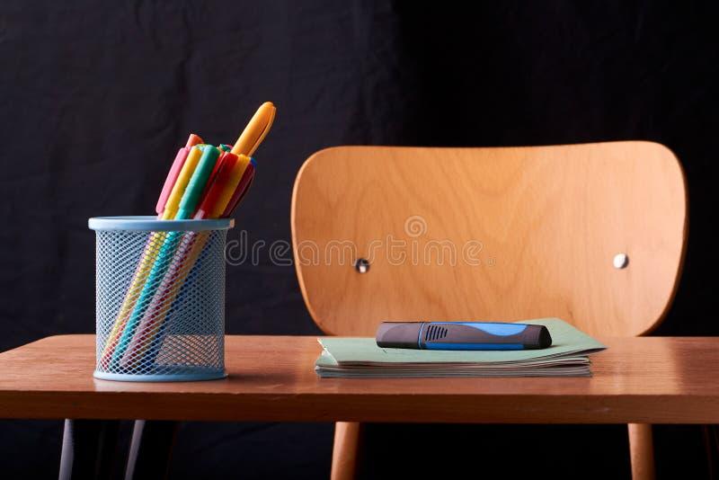 Stylos colorés dans un panier bleu en métal sur le bureau à l'école photographie stock libre de droits