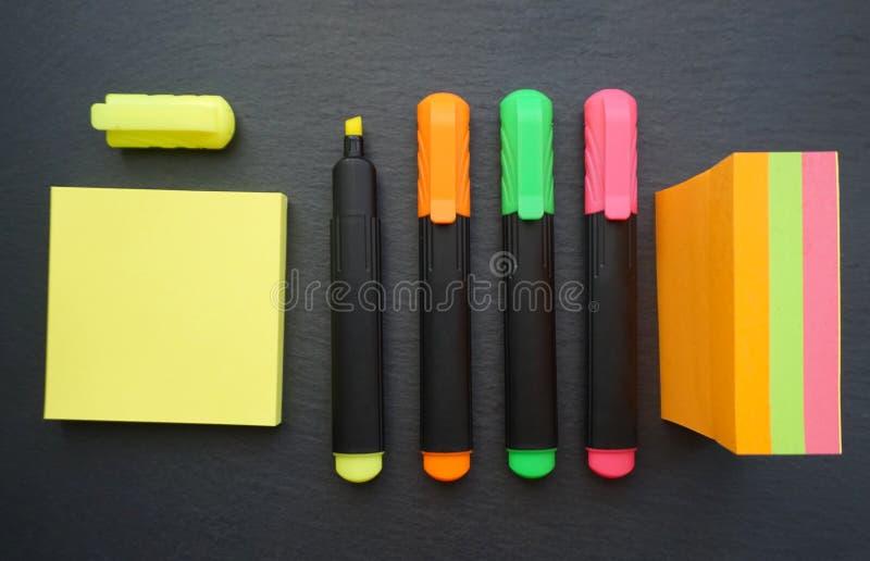 Stylos de marqueur ou revêtement fin dans les diverses couleurs sur le fond noir de conseil avec l'autocollant de note de courrie image stock