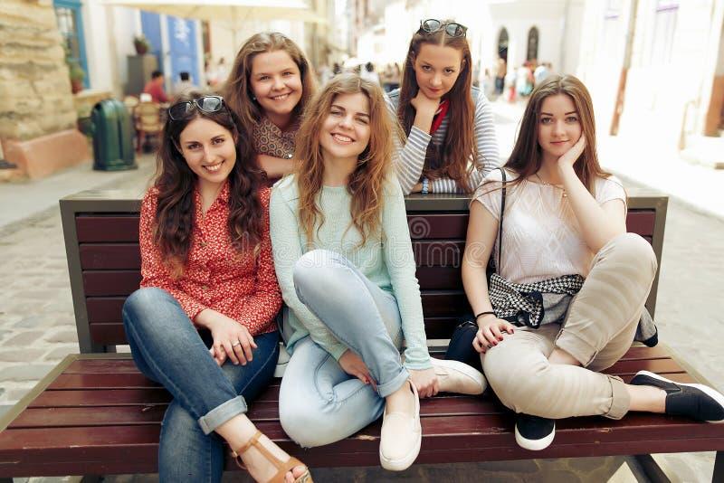 Stylowe, szczęśliwe kobiety hipsterki modne ubrane uśmiechają się i siedzą na ławce na ulicy miasta europy, radosne chwile przyja fotografia royalty free