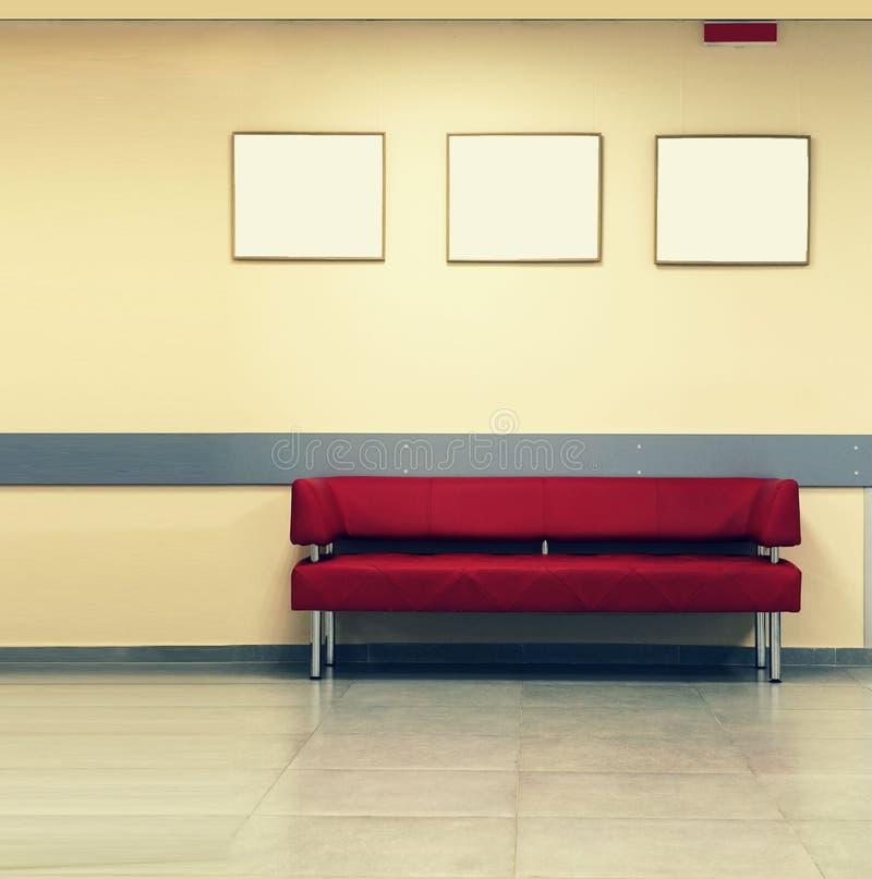 Stylowy minimalizm Czerwona kanapa, wewnętrzny projekt, biuro Pusta poczekalnia z nowożytną czerwoną kanapą przed trzy empt i drz obraz royalty free