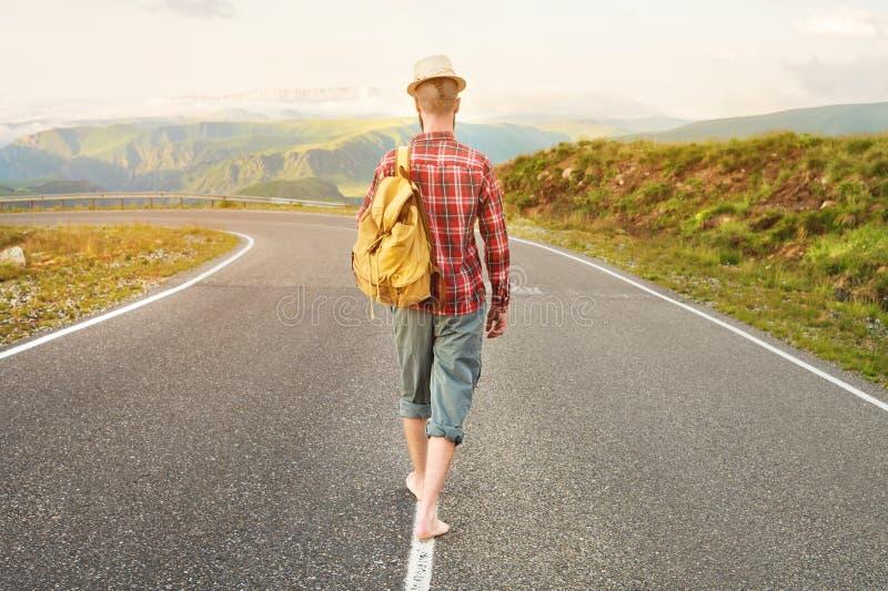 Stylowy podróżnik autostopowicza w kapeluszu z brodą bosaka i z plecakiem spaceruje wzdłuż drogi krajowej zdjęcia stock