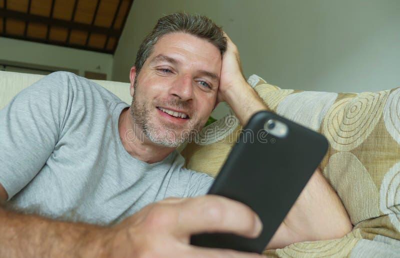 Stylu życia indoors w domu portret młoda szczęśliwa i atrakcyjna mężczyzna kanapy leżanka używać internetów ogólnospołecznych śro fotografia royalty free