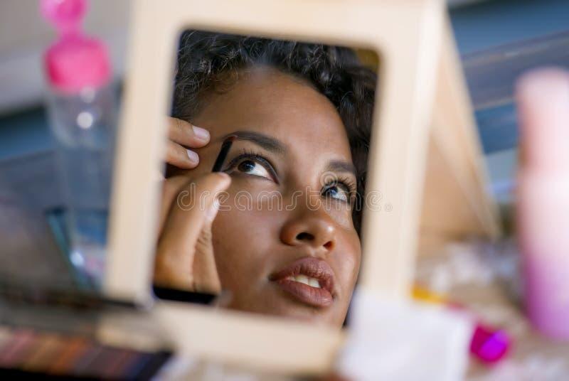 Stylu życia lustrzanego odbicia portret młoda szczęśliwa i piękna latyno-amerykański kobieta używa brew ołówkowego rysunek kontur zdjęcia stock