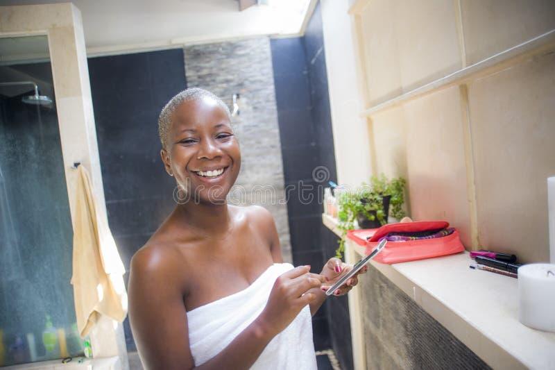 Stylu życia naturalny portret młoda szczęśliwego i atrakcyjnego interneta nałogowa afro Amerykańska kobieta w domowej łazience za zdjęcia stock