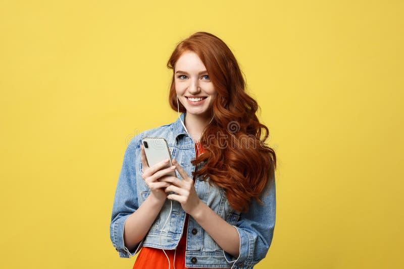Stylu życia pojęcie: Piękna młoda kobieta słucha muzyka na jasnożółtym tle w hełmofonach fotografia royalty free