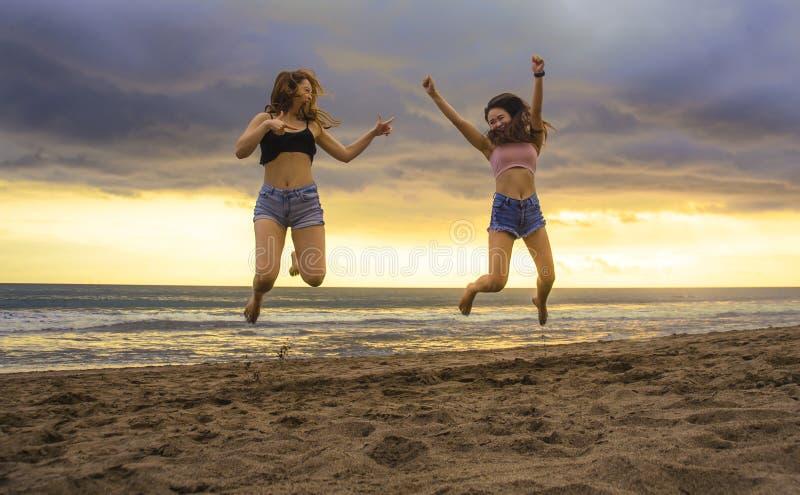 Stylu życia portret dwa szczęśliwy i atrakcyjne młode Azjatyckie Koreańskie kobiet dziewczyny skacze na zmierzch plaży e excited  obrazy stock