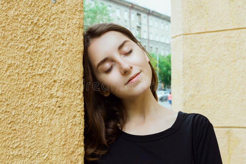 Stylu życia portret młoda dorosła kobieta z ona oczy zamykał przed kolor żółty ścianą fotografia royalty free