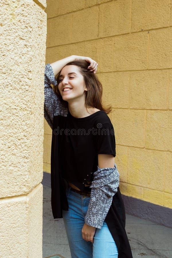 Stylu życia portret szczęśliwa młoda dorosła kobieta śmia się przed kolor żółty ścianą zdjęcia stock