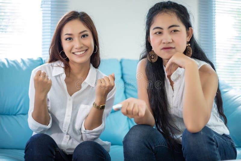Stylu ?ycia portreta Azjatyckie kobiety najlepsi przyjaciele - ono u?miecha si? szcz??liwy na kanapie przy ?ywym pokojem zdjęcie stock