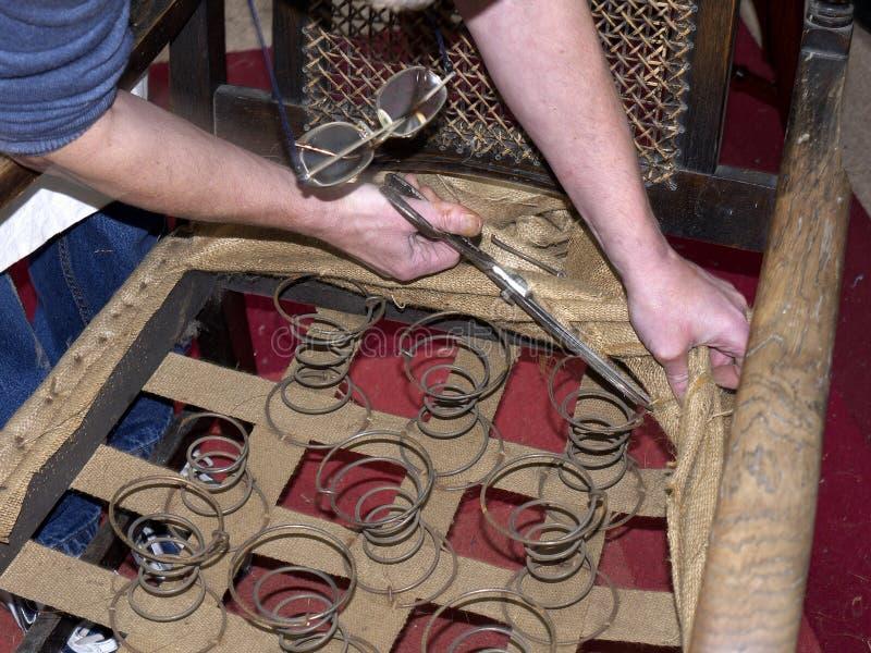 Styra tapetseraren som återställer den antika stolen royaltyfri fotografi