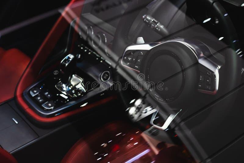 Styrhjulet och inre av den lyxiga sportbilen Sikt till och med vindrutafönstren av den styrninghjulet och instrumentbrädan in royaltyfri fotografi
