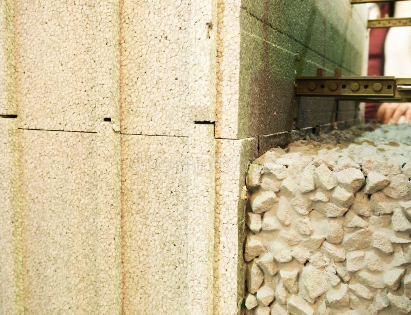 Styrofoam bloki i wzmacniający cement z kamieniami, Izoluje betonowych form ICF materiały dla dom ściany konstruują budynek obraz royalty free