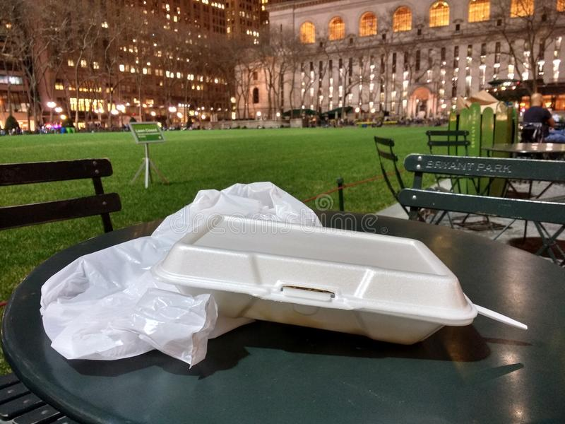 White Foam Take Out Container, Bryant Park, Manhattan, NYC, NY, USA. Styrofoam container, plastic bag, and utensil left after eating gyro over rice bought at a royalty free stock photo