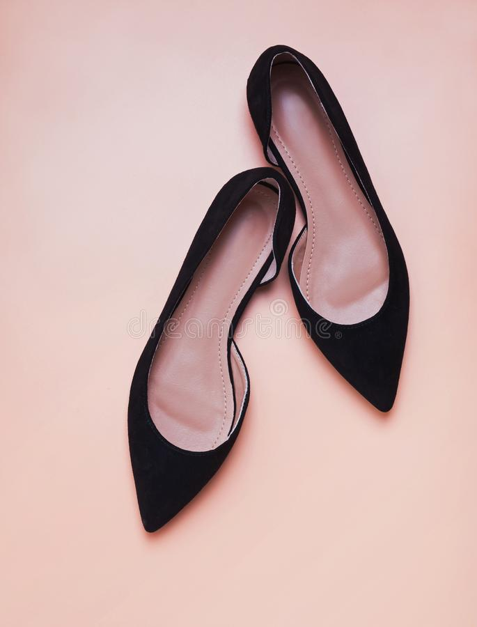 Su?de noir f?minin shoese sur le fond de couleur de p?che photographie stock libre de droits