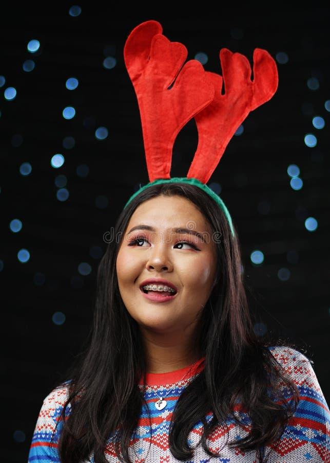 Suéter de la Navidad de la muchacha asiática y venda de los cuernos del reno que llevan imagen de archivo libre de regalías