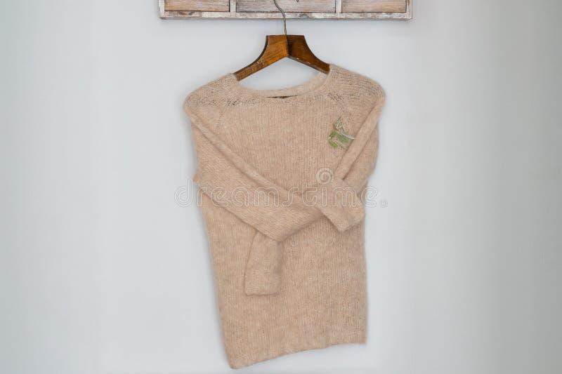 Suéter de lana hecho punto beige en una suspensión fotografía de archivo