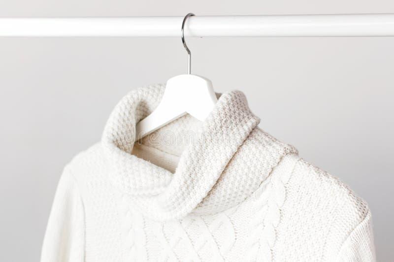Suéter hecho punto blanco de las lanas en una suspensión de madera blanca contra la perspectiva de la pared ligera Ropa del otoño imagen de archivo