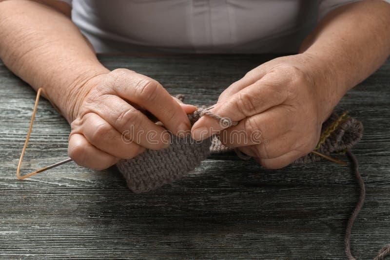 Suéter que hace punto de la mujer mayor en la tabla, primer imagen de archivo