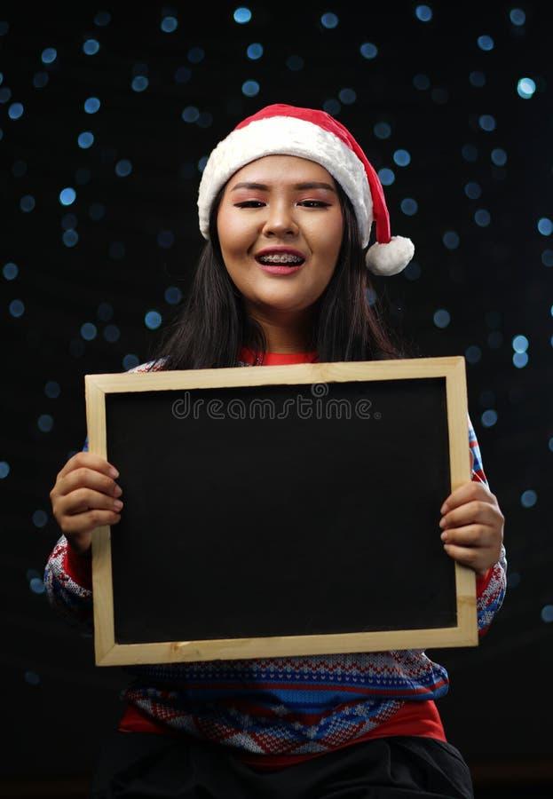 Suéter y Santa Hat Holding Black de la Navidad de la muchacha que llevan asiática fotos de archivo libres de regalías