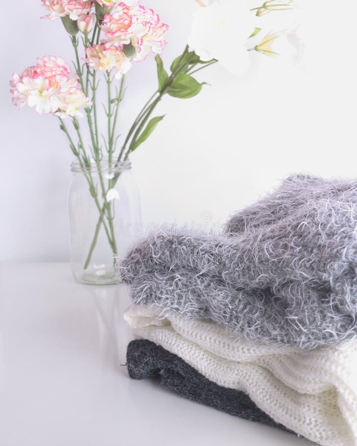 Suéteres del blanco gris y del negro en un escritorio blanco Flores rosadas decorativas en un tarro Ropa otoñal e hivernal imagenes de archivo