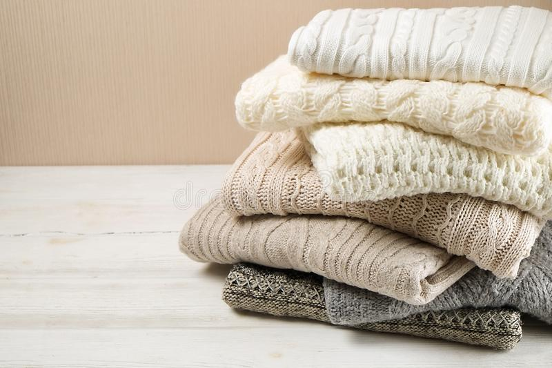Suéteres en colores pastel doblados en la tabla de madera blanca imagen de archivo libre de regalías