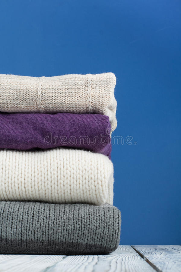 Suéteres hechos punto de las lanas La pila de invierno hecho punto, otoño viste en el fondo azul, de madera, suéteres, géneros de fotografía de archivo libre de regalías