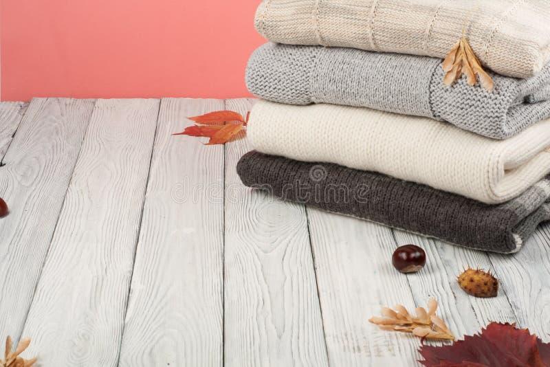 Suéteres hechos punto de las lanas La pila de invierno hecho punto, otoño viste en el fondo de madera, suéteres, géneros de punto imagen de archivo libre de regalías