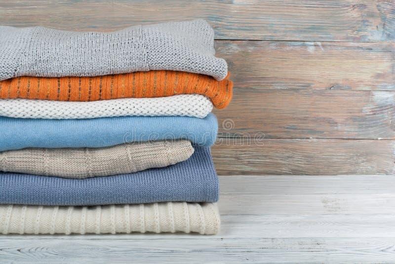 Suéteres hechos punto de las lanas La pila de invierno hecho punto viste en el fondo de madera, suéteres, géneros de punto, espac foto de archivo libre de regalías