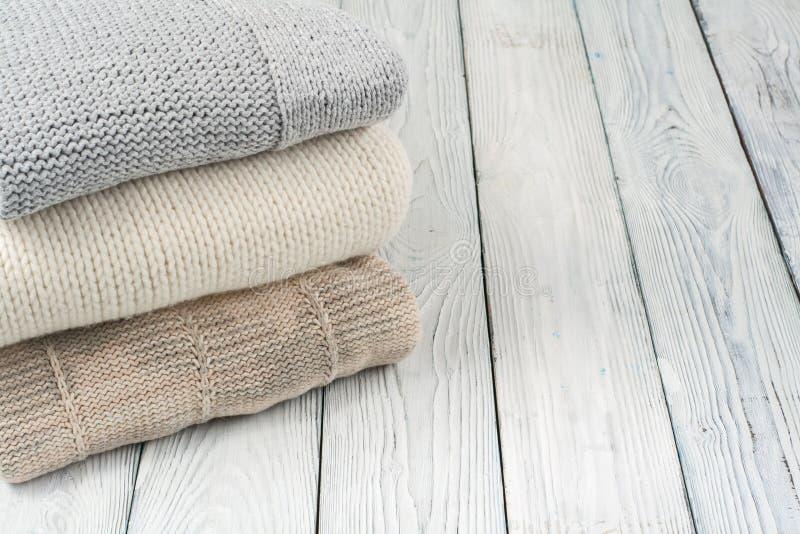 Suéteres hechos punto de las lanas La pila de invierno hecho punto viste en el fondo de madera, suéteres, géneros de punto, espac imagen de archivo