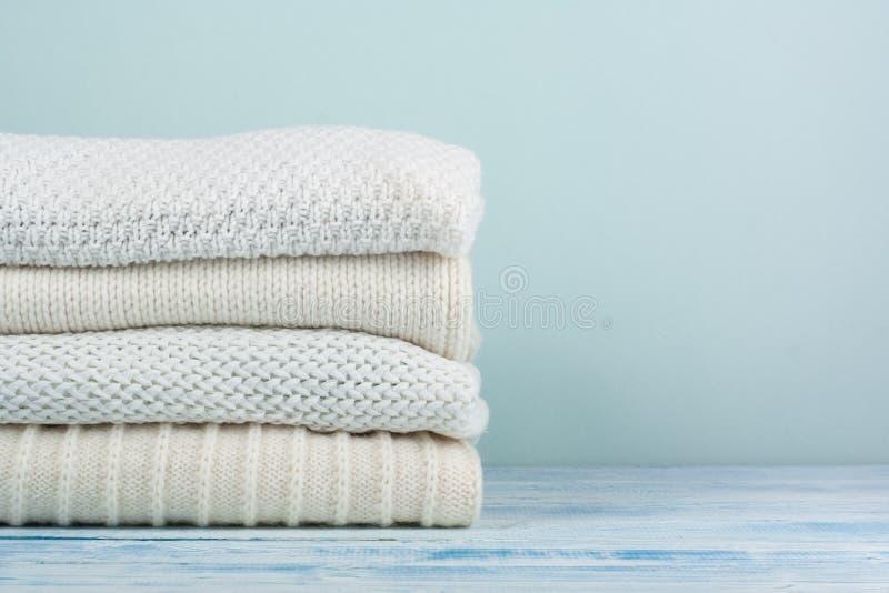 Suéteres hechos punto de las lanas La pila de invierno viste en fondo de madera verde, los géneros de punto, espacio para el text fotografía de archivo