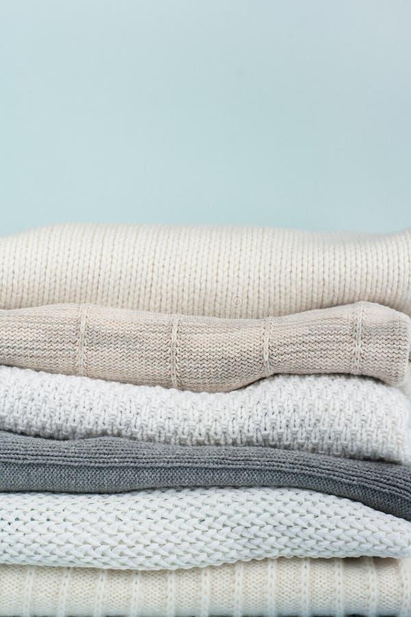 Suéteres hechos punto de las lanas La pila de invierno viste en fondo de madera verde, los géneros de punto, espacio para el text imágenes de archivo libres de regalías