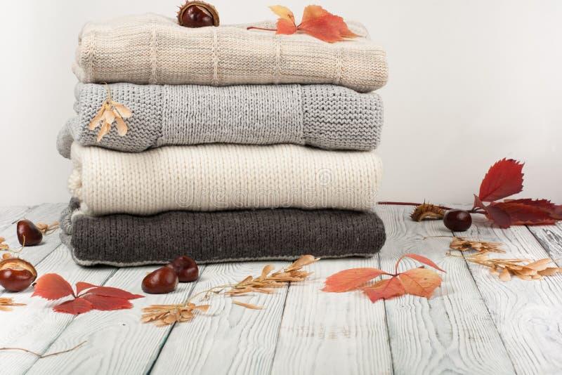 Suéteres hechos punto de las lanas La pila de invierno hecho punto, otoño viste en el fondo de madera, suéteres, géneros de punto imagenes de archivo