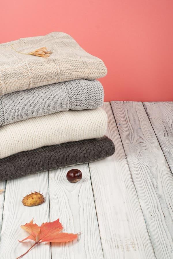 Suéteres hechos punto de las lanas La pila de invierno hecho punto, otoño viste en el fondo de madera, suéteres, géneros de punto fotografía de archivo