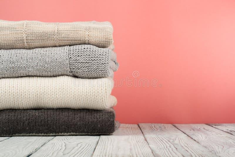 Suéteres hechos punto de las lanas La pila de invierno hecho punto, otoño viste en el fondo rojo, de madera, suéteres, géneros de fotos de archivo