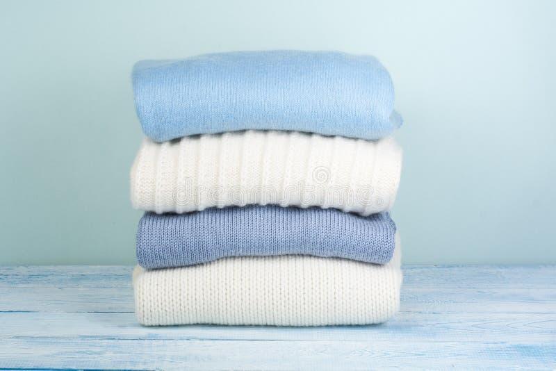 Suéteres hechos punto de las lanas La pila de invierno hecho punto, otoño viste en el fondo verde, de madera, suéteres, géneros d imagen de archivo libre de regalías