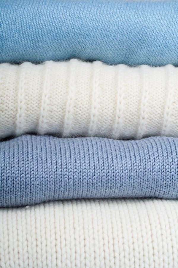Suéteres hechos punto de las lanas La pila de invierno hecho punto, otoño viste en el fondo verde, de madera, suéteres, géneros d fotografía de archivo libre de regalías